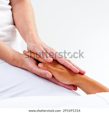 Macro close up of therapist hands holding female hand.Healing treatment at reiki session. - stock photo