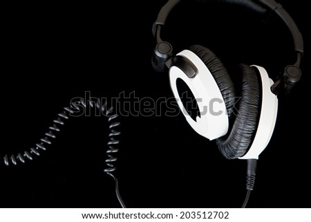 Macro close up still life detail view of a pair of high end professional quality headphones isolated against a black background. Interior stereo listening equipment device with spiral cable. - stock photo