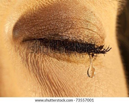 Macro closeup of a female eye with teardrop in soft light - stock photo