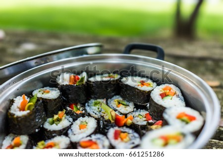 Macro closeup of metal pot filled with maki sushi with avocado, carrots and red bell pepper