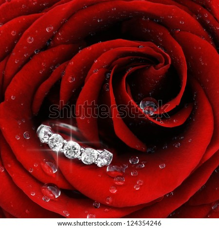 Macro closeup of red rose with dew drops and beautiful sparkling diamond ring - stock photo
