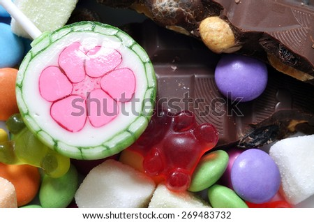 Macro detail of lollipop, gummy bears, chocolate and sour candy on colored smarties background - stock photo