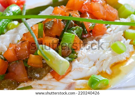 macro fish dish is exquisitely decorated on a white plate with lemon and vegetables