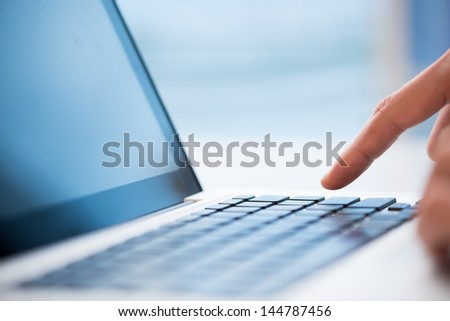 Macro image of a finger being about to press a key on a laptop keyboard - stock photo