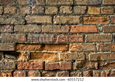Macro image of an old, distressed stone brick wall with chips and scratches for texture or background. - stock photo