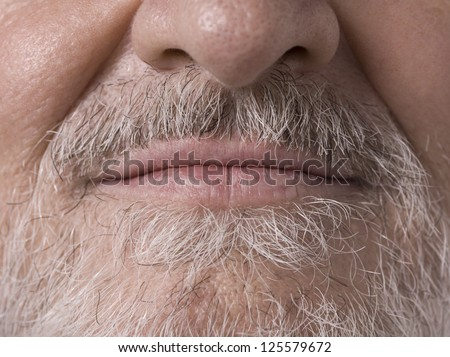 Macro image of an old man face with the camera focused on his bearded mouth - stock photo