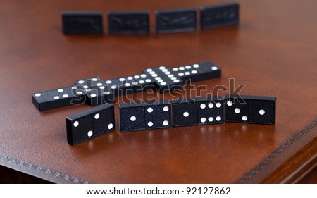 Macro image of dominos on a leather table in the middle of a game - stock photo
