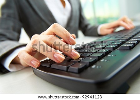 Macro image of human hand with forefinger going to press key on keyboard - stock photo