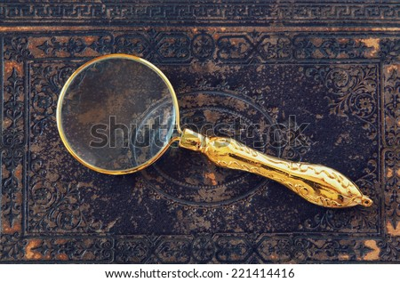 macro image of magnifying glass over antique black cover. - stock photo