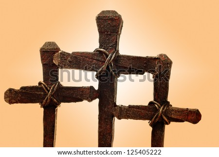 Macro image of rusty nail crosses on gradient background with copy space. - stock photo
