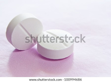 Macro image of two white isolated medicinal tablets. - stock photo