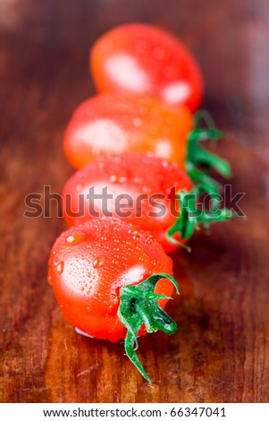 macro images of four wet tomatoes closeup on wooden table - stock photo