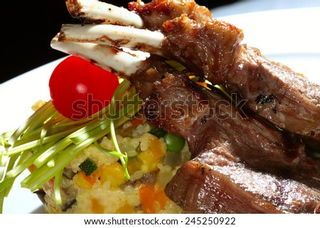 macro meat on the bone grilled with vegetables and cream sauce on a white plate - stock photo