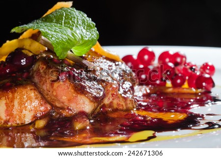 macro meat with sauce and vegetables on a white plate on a dark background studio - stock photo