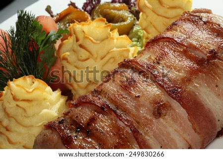 macro meatloaf with bacon and potato gratin decorated with greens and pickles - stock photo