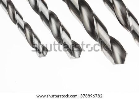 Macro metal drill bit isolated on white background. Steel drills HSS (High Speed Steel) - stock photo