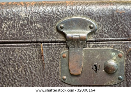 Macro of a locked metal latch of an antique suitcase - stock photo