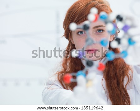 macro of a student in a chemistry lab holding in hands and analyzing DMT molecular model - stock photo