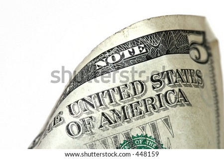 macro of a used american five dollar bill. relatively shallow depth of field with processing to obtain a grunge-type of look. - stock photo
