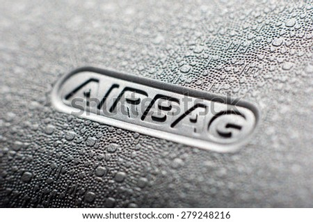 Macro of an airbag sign on a dashboard.