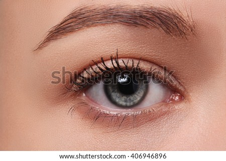 Macro of beautiful female eye with perfect shape eyebrows. Clean skin, fashion naturel make-up.