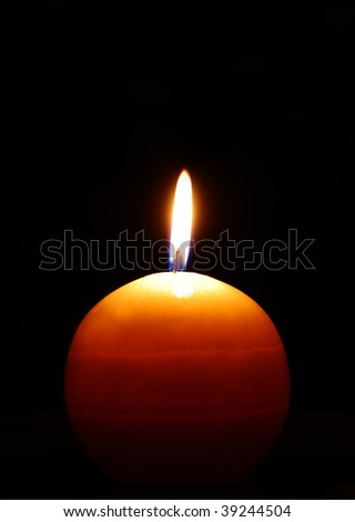 Macro of burning candle isolated on black background