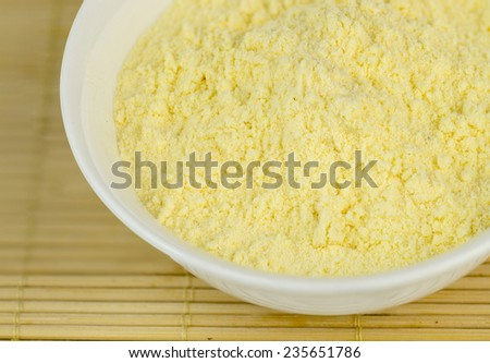 Macro of corn flour in bowl - stock photo