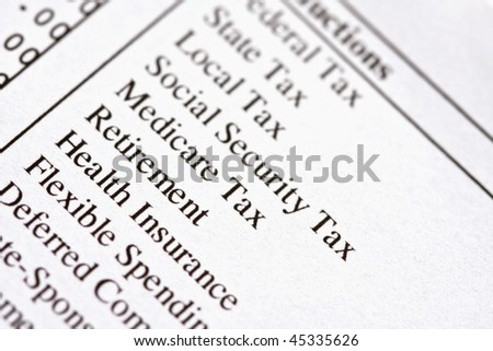 Macro of deductions on a paycheck. - stock photo