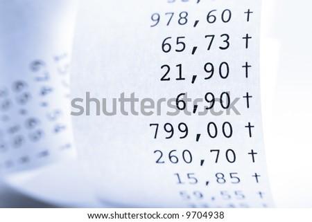 Macro of folded receipt paper. Shallow DOF. Blue tone. - stock photo