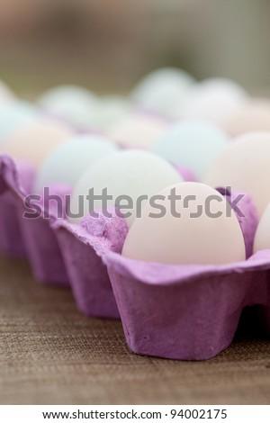 Macro of free range organic eggs in a purple crate. - stock photo