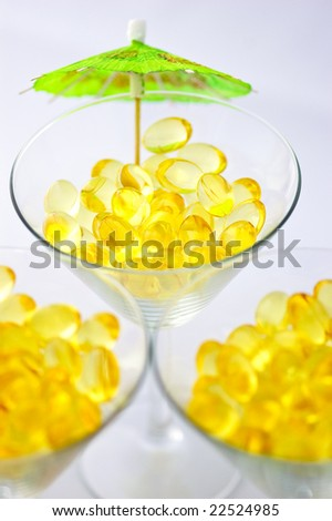 Macro of omega-3 capsules served as drinks on three martini glasses
