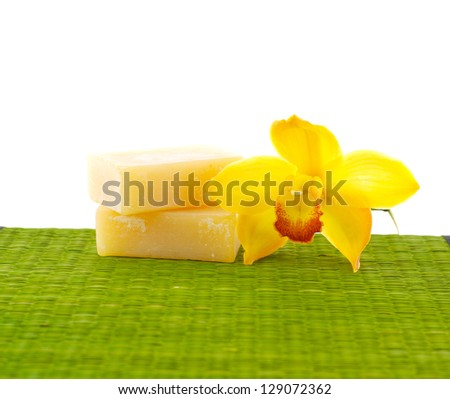 Macro of orchid with natural handmade soap on green mat - stock photo