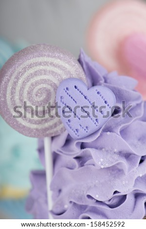 macro of purple cupcake topping with candy heart and lollipop - stock photo