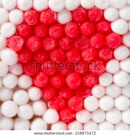 Macro of red and white cotton swabs forming a heart shape - Shallow depth of field - stock photo