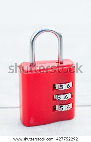 Macro of red combination lock on wooden table - stock photo