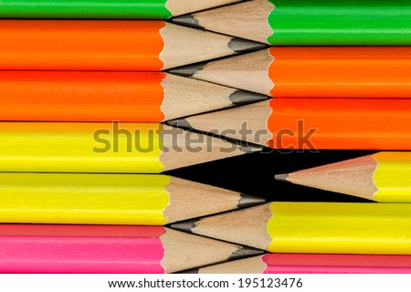 macro of rows of neon colored pencils isolated on black - stock photo