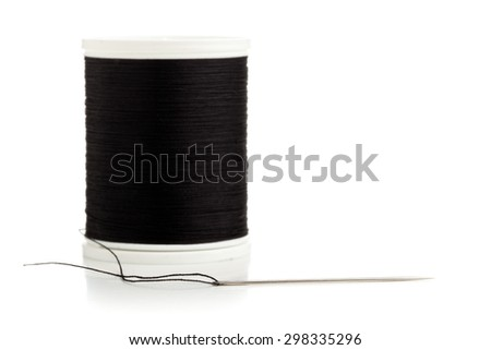 Macro of sewing needle and black thread on white background - stock photo