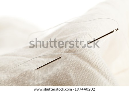 Macro of sewing needle in white fabric - stock photo
