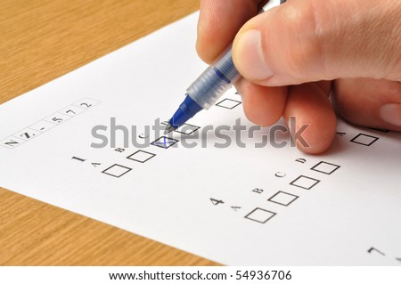 Macro of someone's hand filling exam answers form