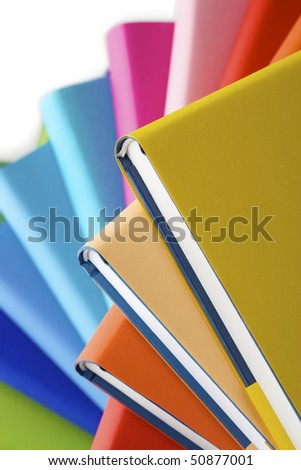 Macro of spiral stack of colorful real books, yellow book on top. - stock photo