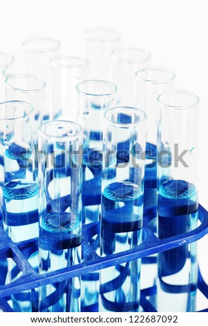 Macro of test tubes filled with blue liquid or chemical, great science, health or discovery background. - stock photo