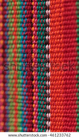Macro of textured colorful blue, purple, pink, red, yellow and orange fabric background