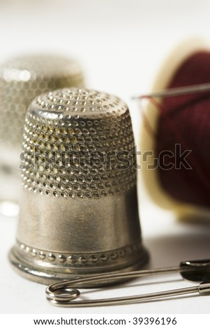 Macro of thimble, safety pin, needle and thread - stock photo
