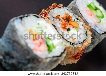 Macro of three different sushi on black background - stock photo