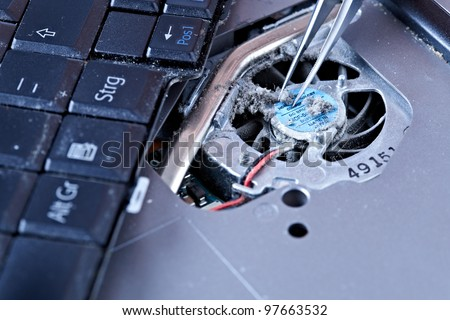 macro of tweezers on a laptop fan - stock photo