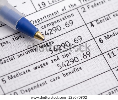 Macro of W2 1040 Form and pen for tax day. - stock photo