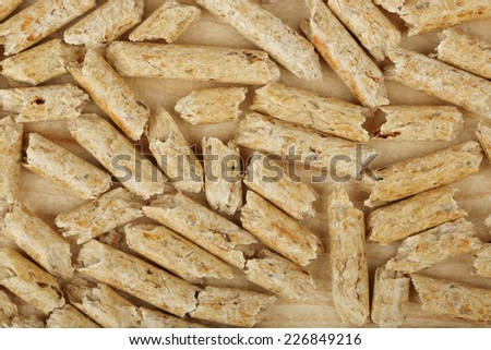 macro of wood pellets on wooden surface - stock photo