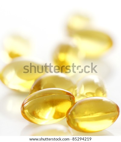 Macro of yellow gelatin pills over white background - stock photo