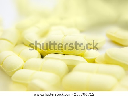 Macro of yellow pills angle view. Shallow DOF, selective focus. Pills and tablets bakground. - stock photo