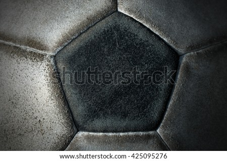 Macro photo of an old black and white soccer ball with pentagons and hexagons in leather - stock photo